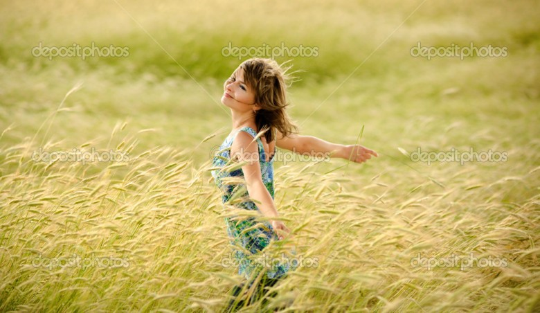 beautiful girl smiling in a field of wheat